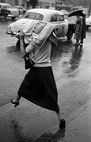 Woman covered by newspaper under the rain